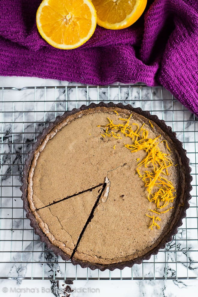 Overhead shot of Dark Chocolate Orange Tart on a wire rack with a slice cut out.
