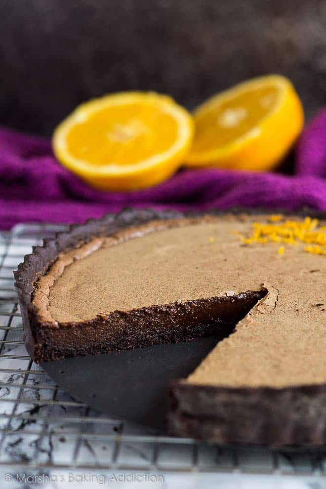 Dark Chocolate Orange Tart on a wire rack with a slice removed to show centre.