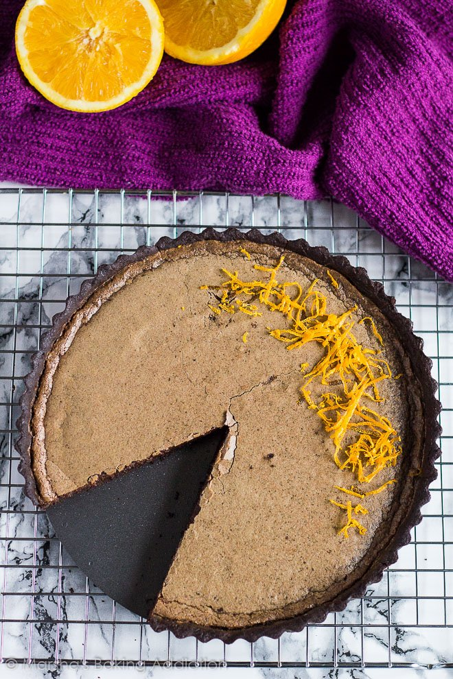 Overhead shot of Dark Chocolate Orange Tart on a wire rack with a slice removed.