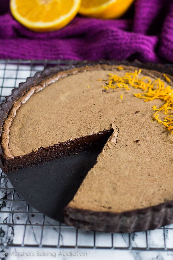 Dark Chocolate Orange Tart on a wire rack with a slice removed.