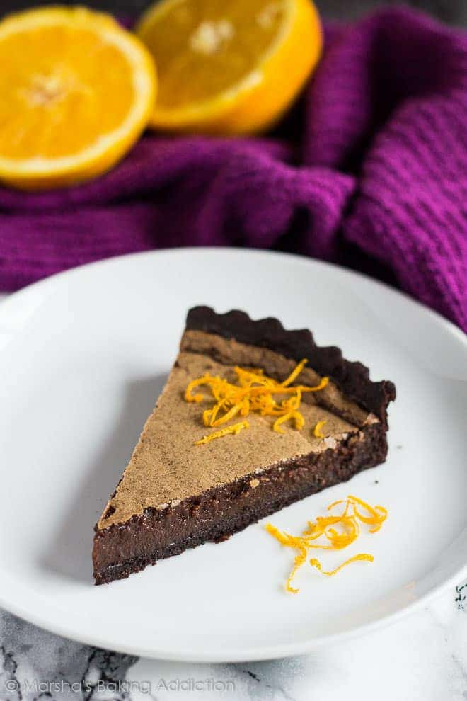 A slice of Dark Chocolate Orange Tarttopped with orange zest served on a white plate.