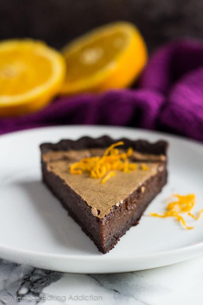 Slice of Dark Chocolate Orange Tarttopped with orange zest on a white plate.
