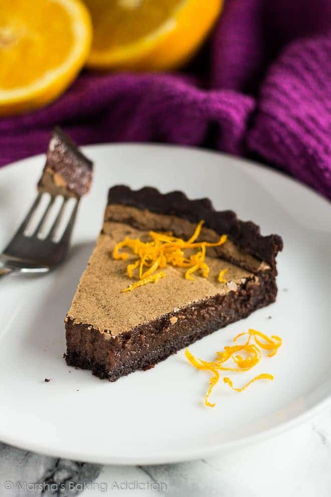 Slice of Dark Chocolate Orange Tarttopped with orange zest on a white plate with a fork.