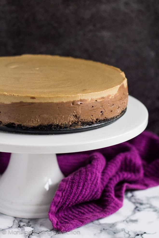 Layered Mocha Cheesecake on a white cake stand.