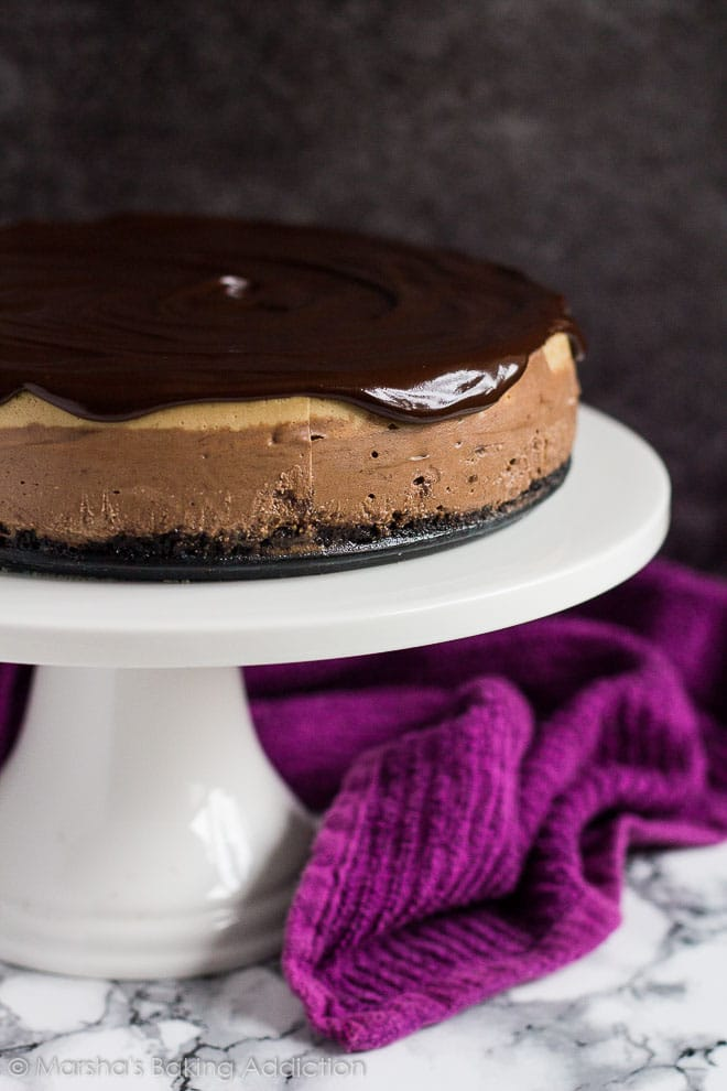 Layered Mocha Cheesecake topped with chocolate ganache on a white cake stand.