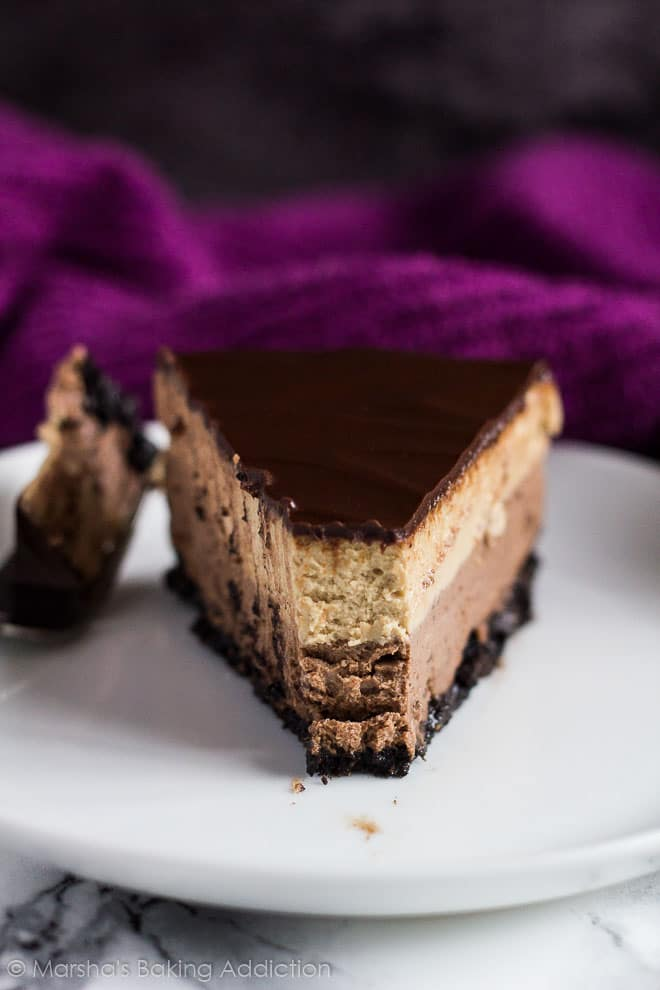 A slice of Layered Mocha Cheesecake on a small white plate with a fork.