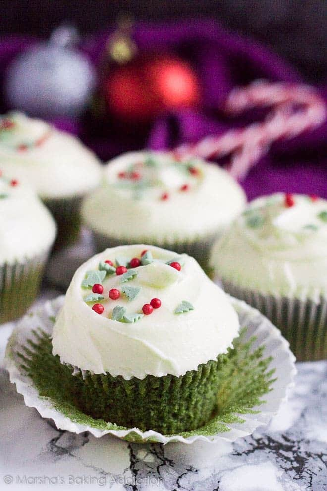 Cream Cheese frosted Green Velvet Cupcake on marble background with wrapper peeled off.