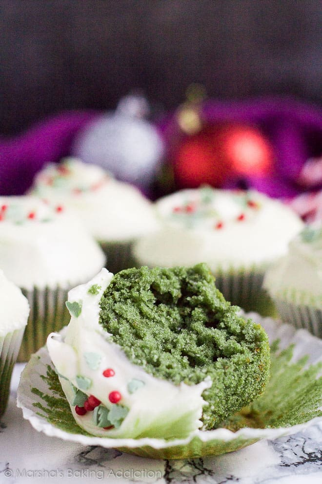 A frosted green velvet cupcake on its side on the wrapper with a bite taken out of it.