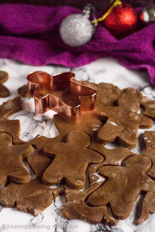 Gingerbread Menshapes being cut out of dough on marble background.