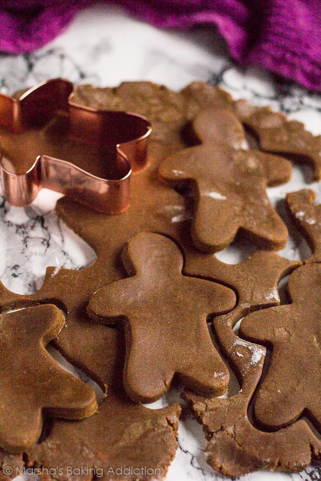 Gingerbread Men shapes being cut out of the dough on marble background.