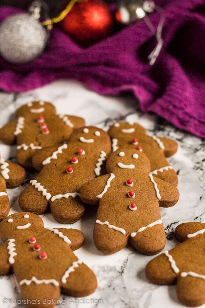 Iced gingerbread men cookies overlapped on marble background.