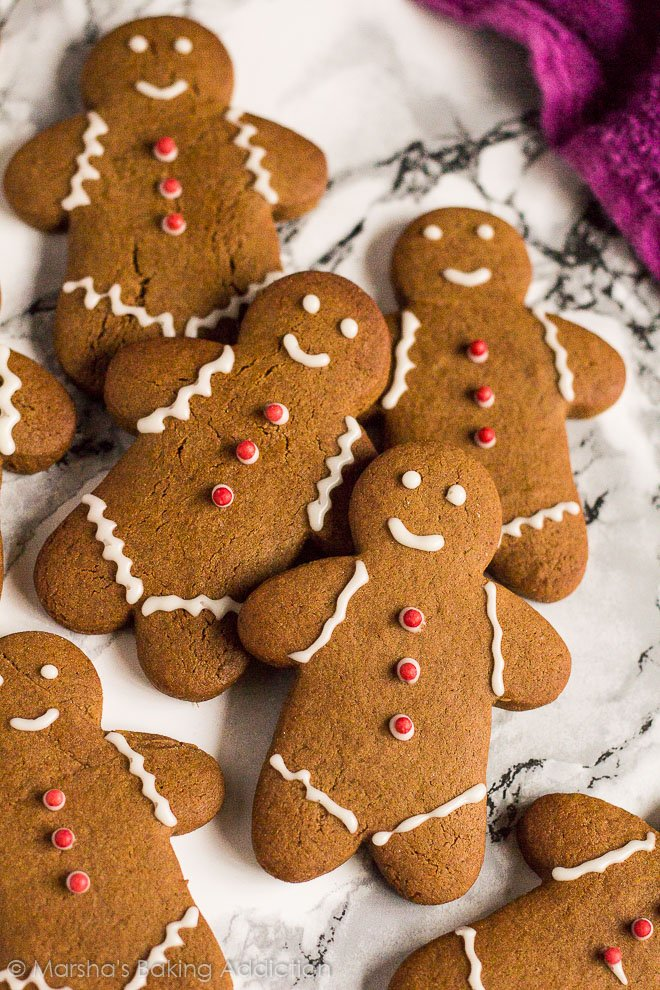 Overhead shot of iced gingerbread men overlapped on marble background.