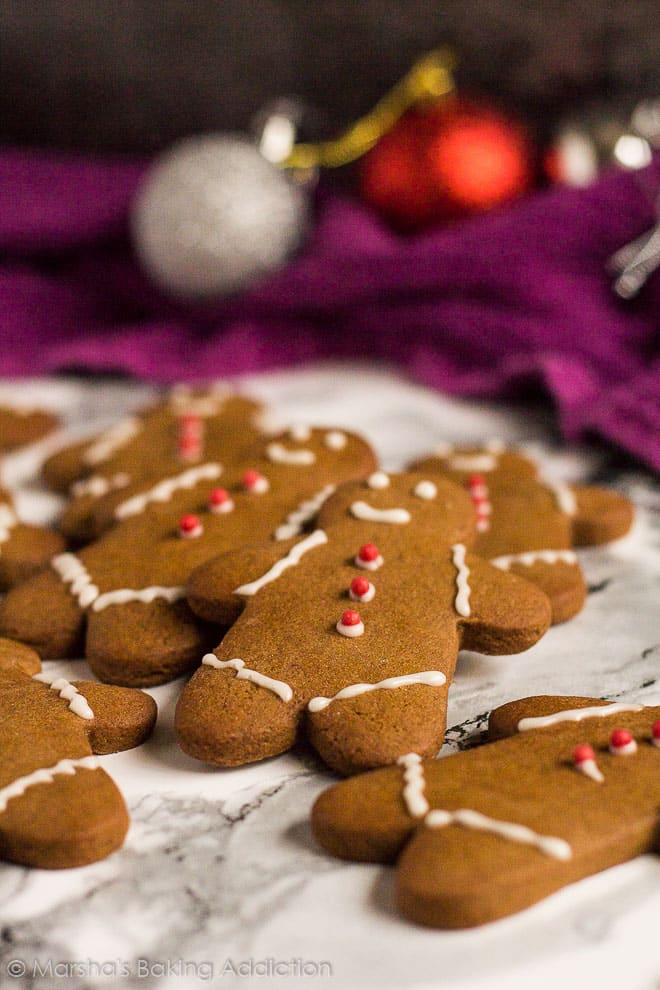 Gingerbread Men on marble background with Christmas baubles in background.