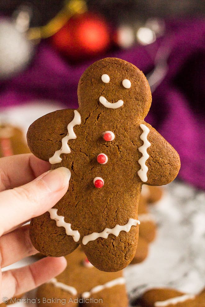 An iced gingerbread man cookie being picked up by hand.