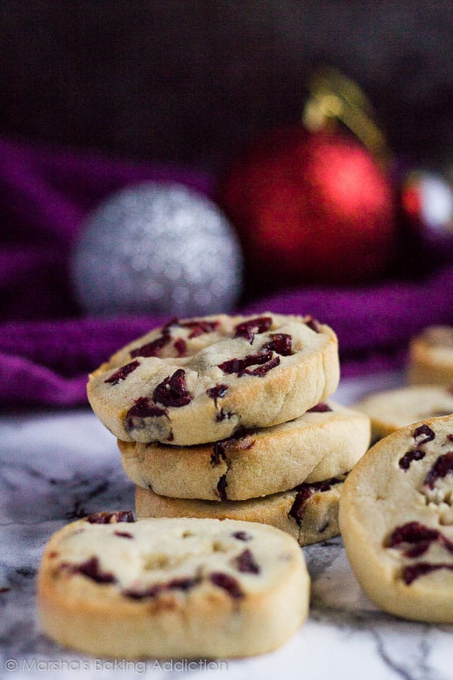 Stack of three Cranberry Orange Slice 'n' Bake Cookies on marble background surrounded by more cookies.