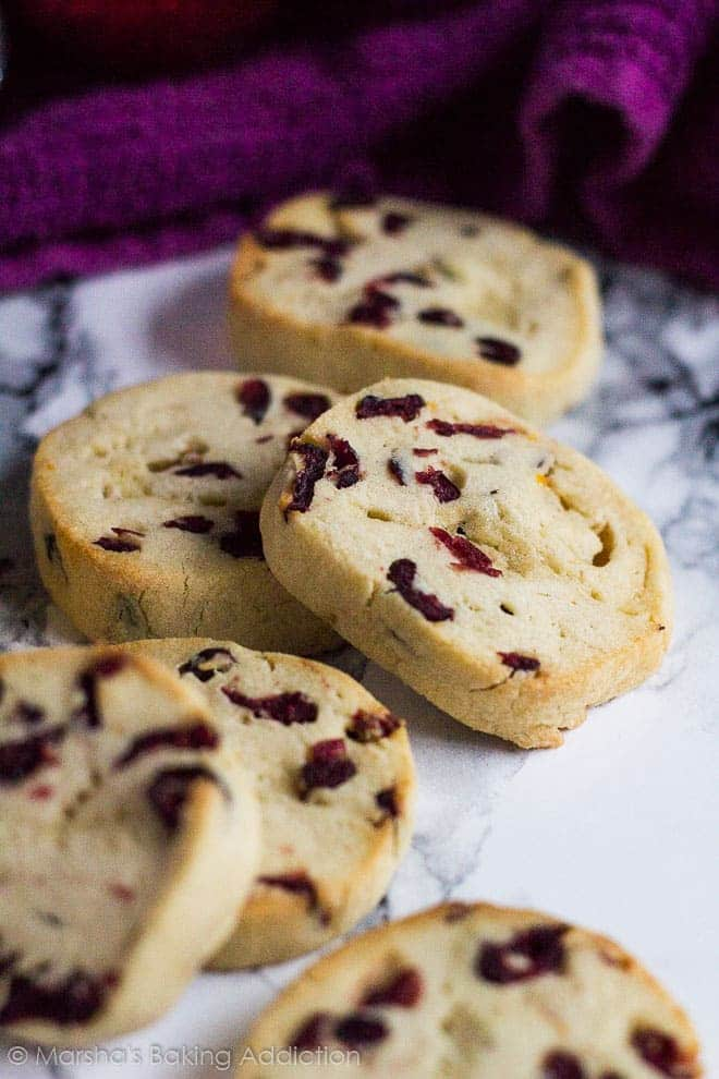 Overlapped Cranberry Orange Slice 'n' Bake Cookies on marble background.