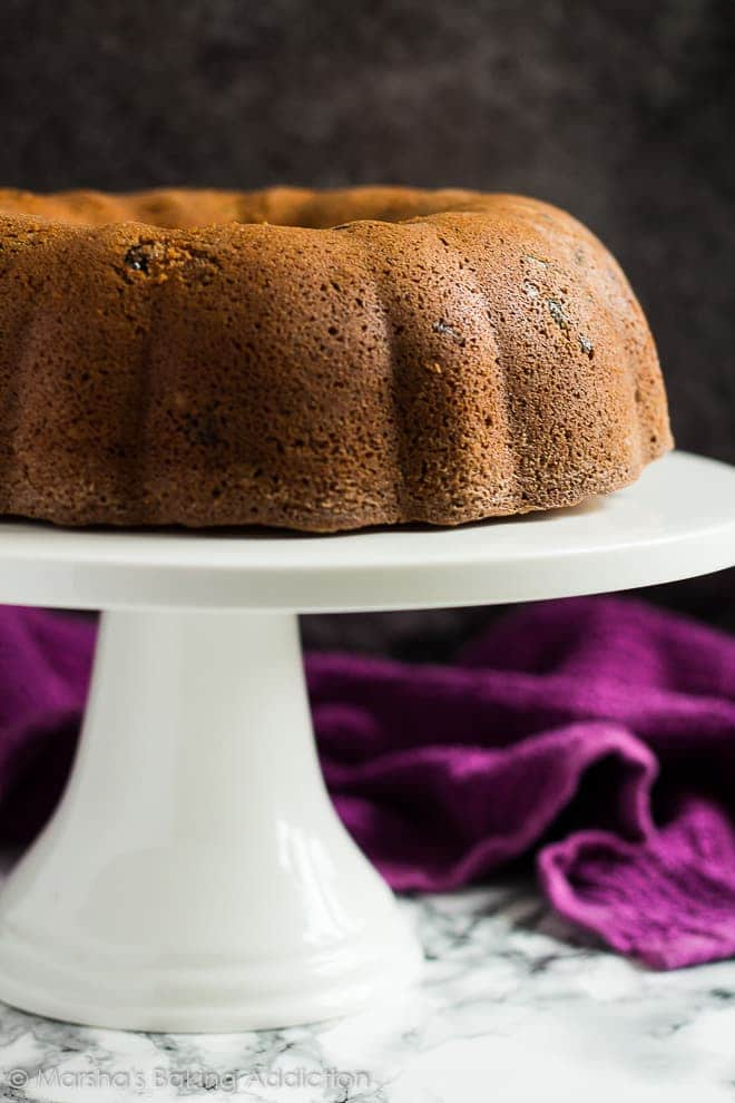 Unglazed cranberry orange bundt cake on a white cake stand.