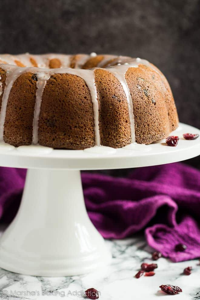A glazed cranberry orange bundt cake on a white cake stand.