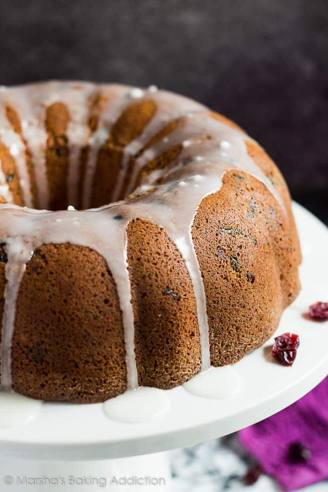 Cranberry orange bundt cake drizzled with a glaze on white cake stand.
