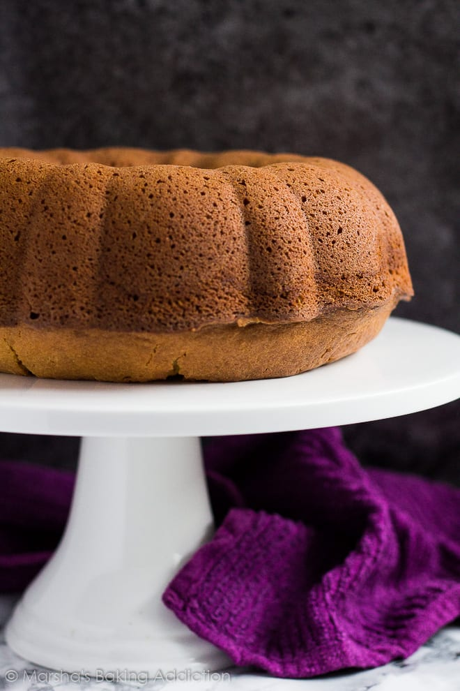 Peanut butter and jam bundt cake with no glaze on a white cake stand.