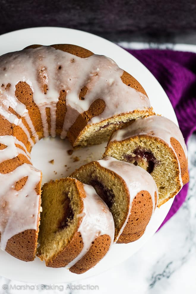 Overhead shot of glazed peanut butter bundt cake with three slices overlapped on white cake stand to show jam filling.