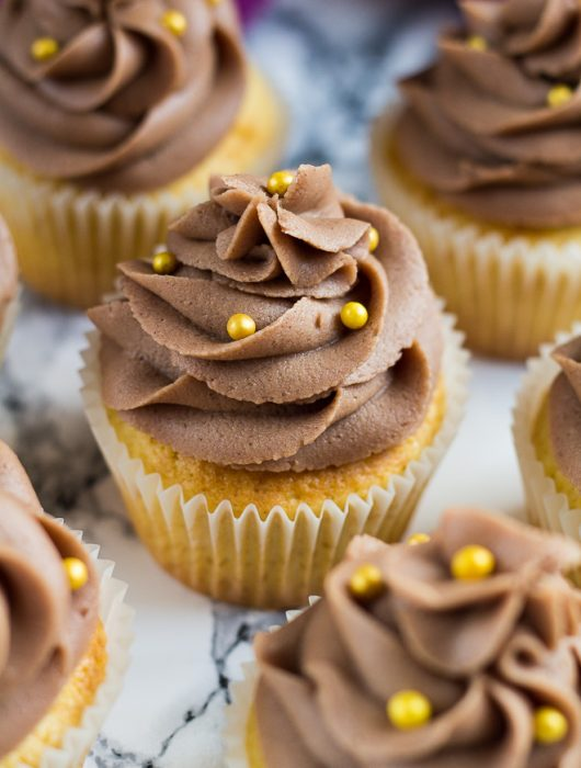 Chocolate buttercream frosted yellow cupcakes with gold ball sprinkles on marble background.