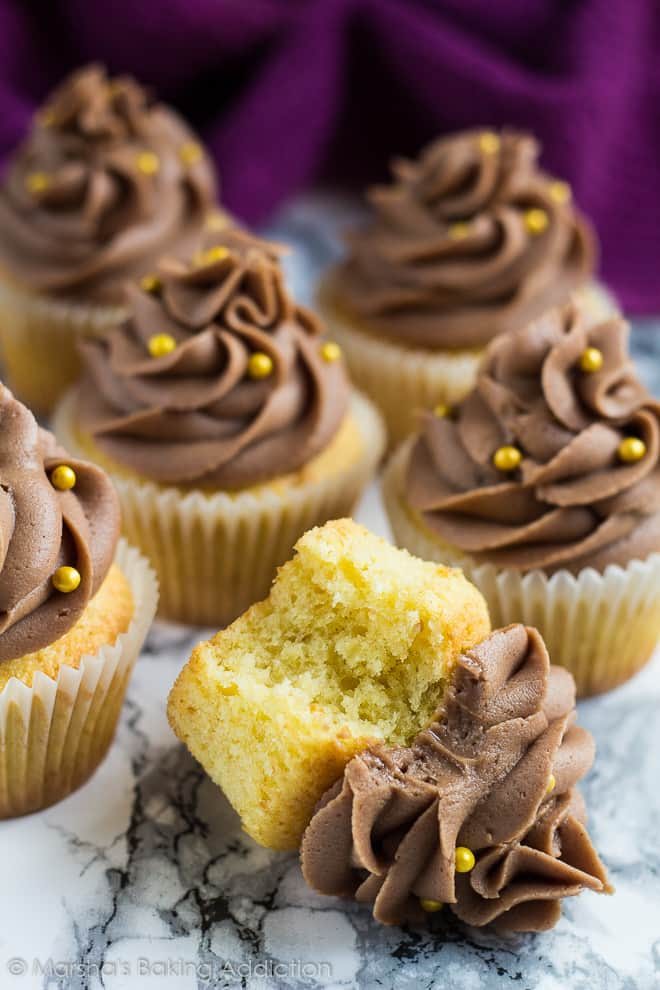 Yellow cupcakes with chocolate buttercream frosting and one on its side with a bite taken out of it.