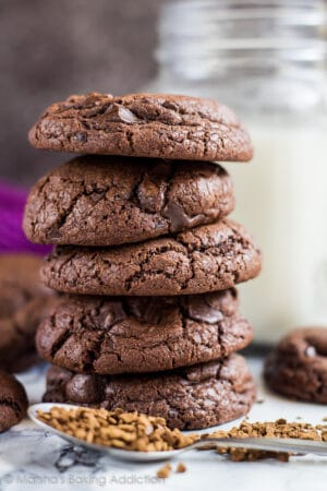 Stack of chocolate chip mocha cookies with a mason jar of milk in background.
