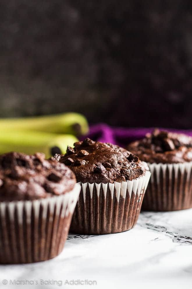 A row of three chocolate banana muffins on marble background.