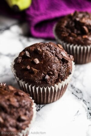 Overhead shot of row of three chocolate banana muffins on marble background.