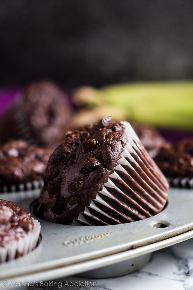 Chocolate banana muffins in a muffin pan with one on its side.