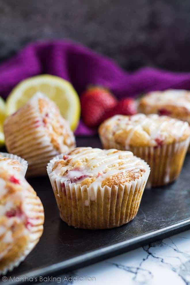 Strawberry lemon muffins drizzled with a glaze on a baking tray.