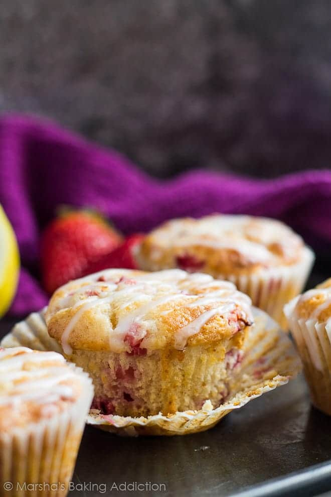 A strawberry lemon muffin drizzled with a glaze with wrapper peeled off on baking tray.