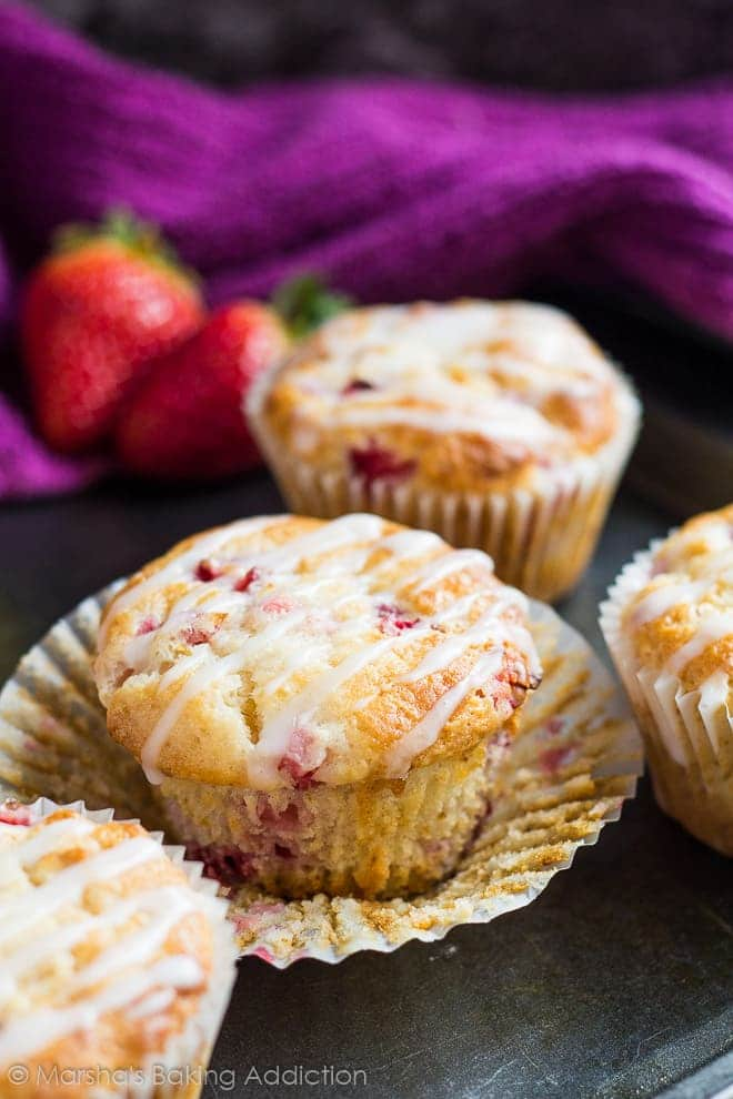 Strawberry lemon muffin with wrapper peeled off on baking tray.