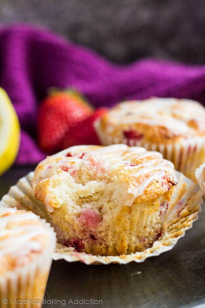 Strawberry lemon muffin with wrapper peeled off and bite taken out of it on baking tray.