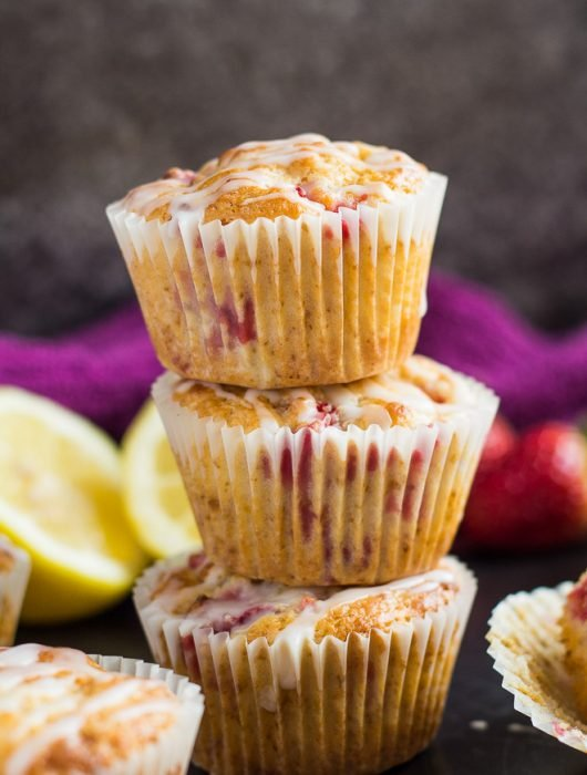 A stack of three strawberry lemon muffins drizzled with a glaze on baking tray.