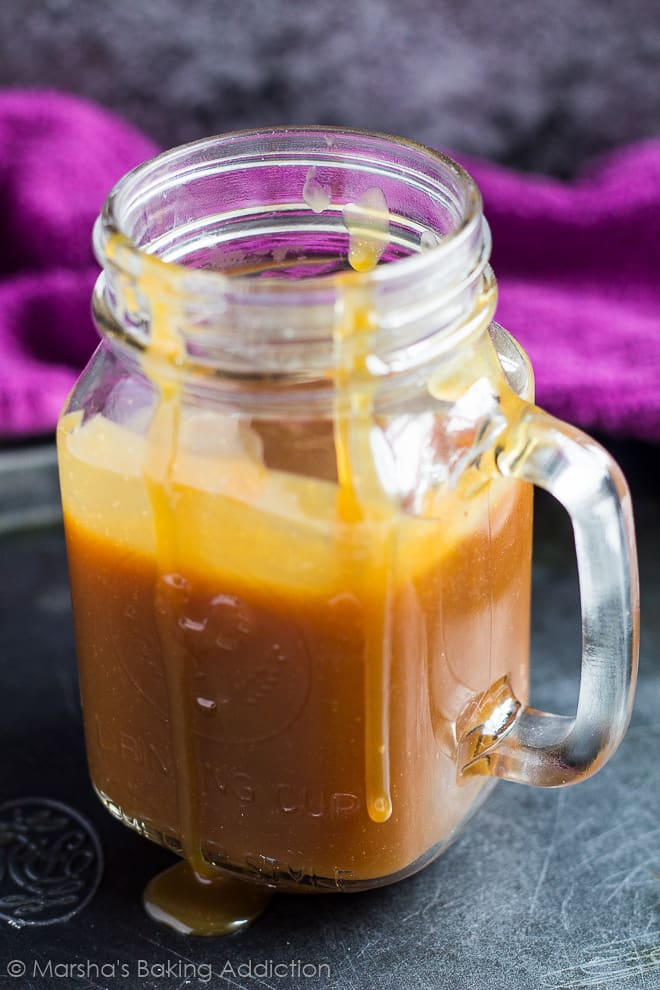 Homemade salted caramel sauce half filling a mason jar with drips going down the side on a baking tray.