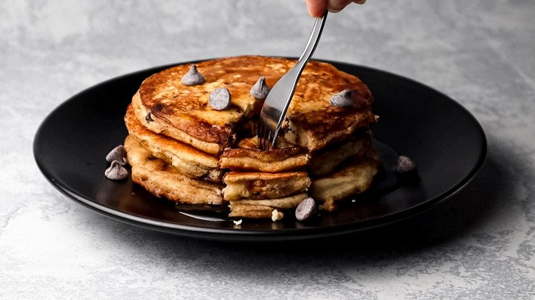 A stack of pancakes served on a plate with maple syrup and chocolate chips.