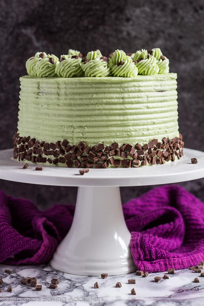 Mint chocolate chip layer cake studded with chocolate chips on a white cake stand.
