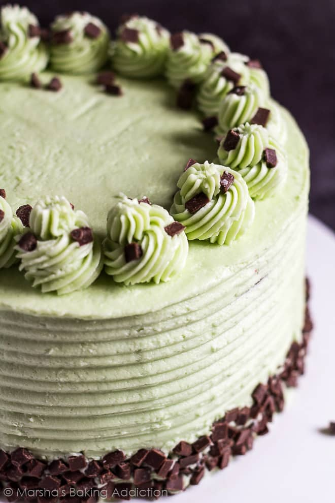 Mint chocolate chip layer cake topped with piped swirls and chocolate chips on a white cake stand.