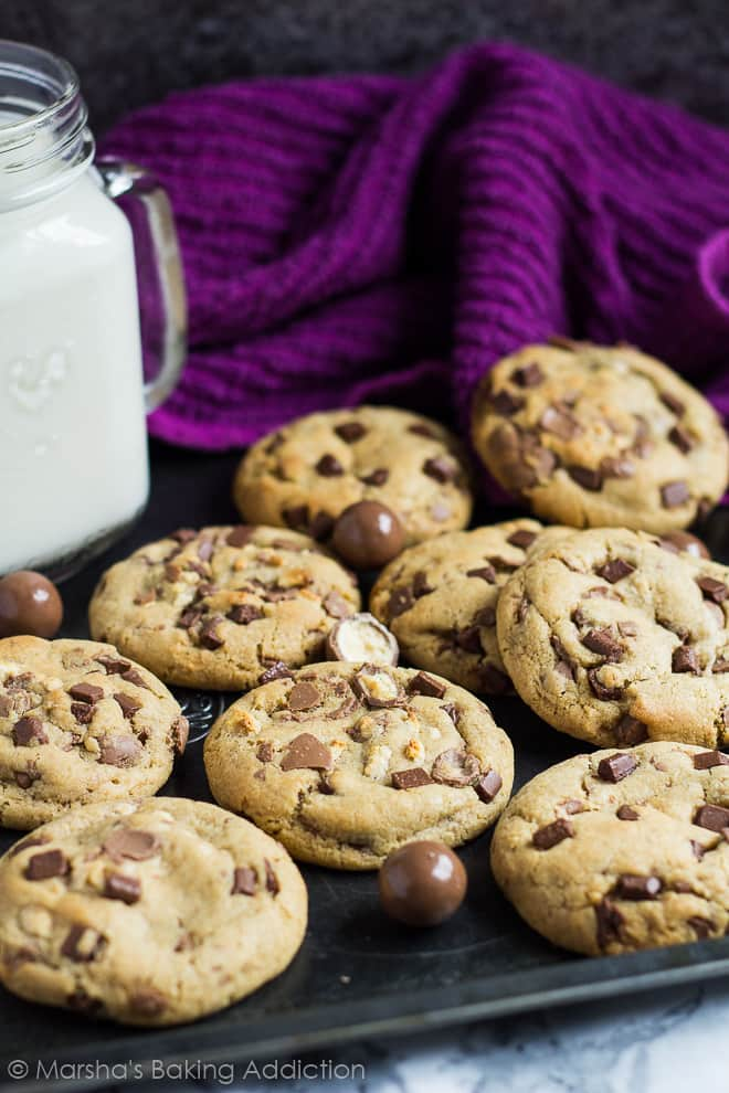 A baking tray full of chocolate chip cookies with Maltesers and a mason jar of milk.