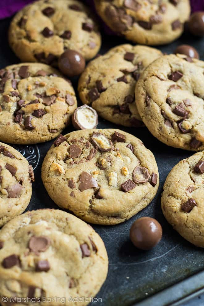 Chocolate chip cookies with Maltesers on a baking tray.