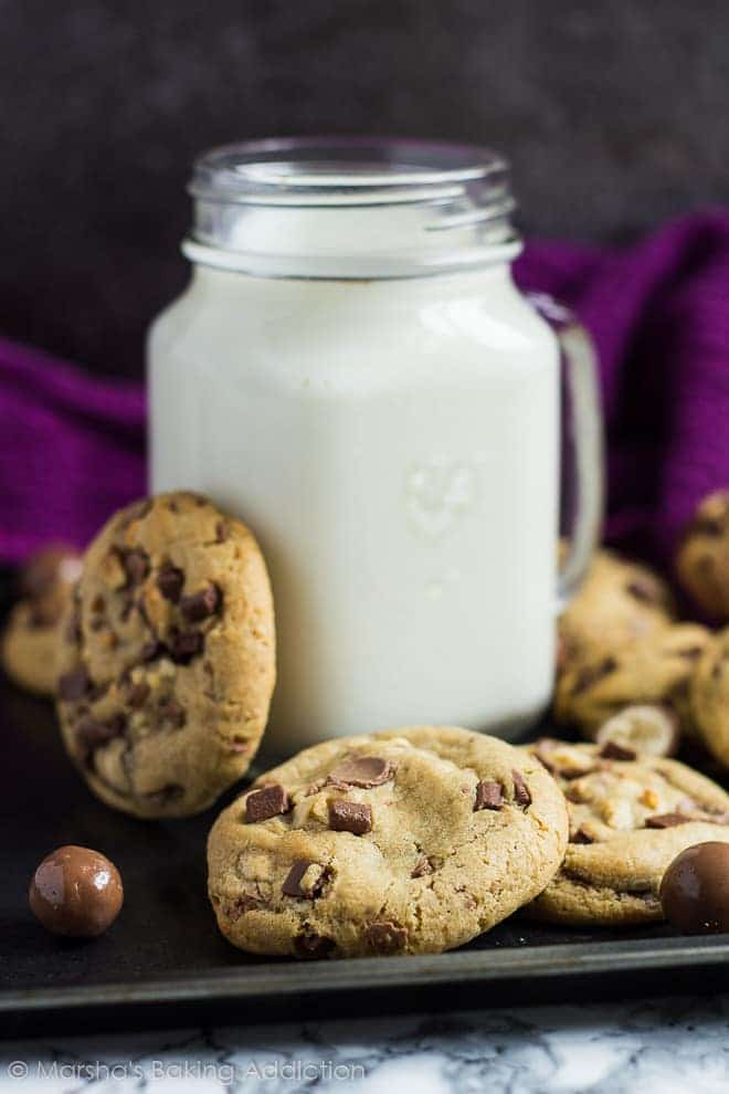 Chocolate chip cookies with Maltesers up against a mason jar of milk on a baking tray.