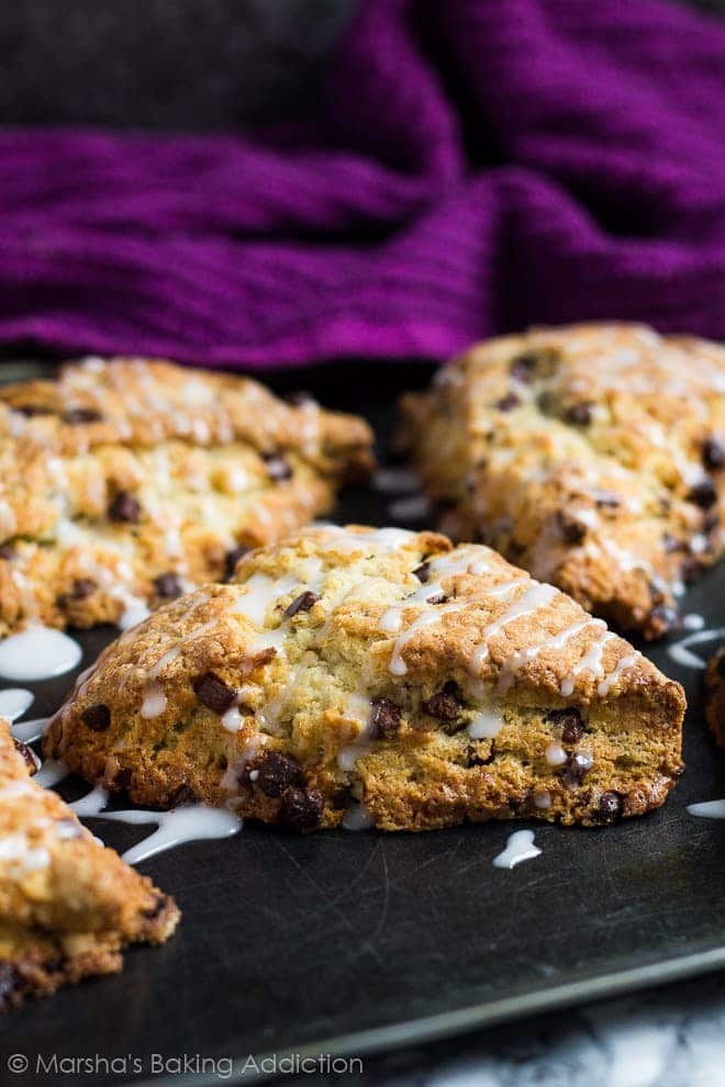 Chocolate chip studded scones drizzled with a glaze on a baking tray.
