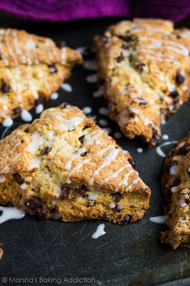 Chocolate chip scones drizzled with a glaze on baking tray.