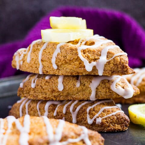 A stack of three thick lemon scones drizzled with a glaze and topped with lemon slices on a baking tray.