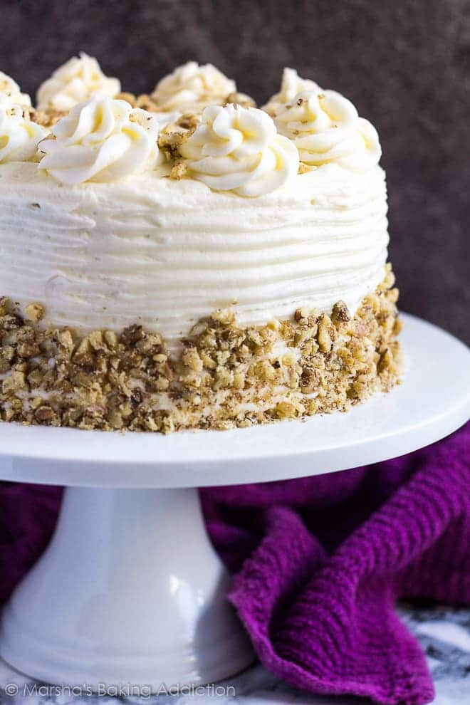 Carrot layer cake with cream cheese frosting and studded with crushed pecans on a white cake stand.