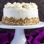 A cream cheese frosted carrot layer cake studded with crushed pecans on a white cake stand.