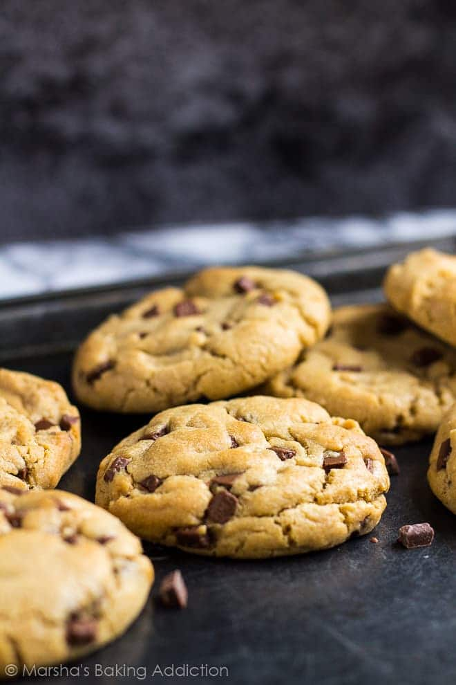 Thick chocolate chip peanut butter cookies on a baking tray.