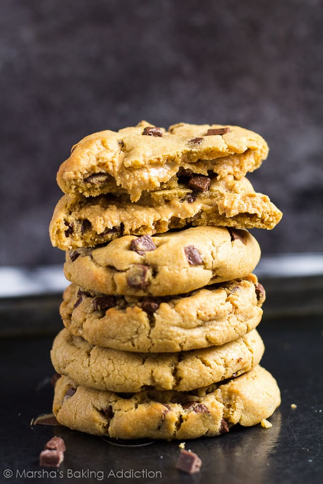 A tall stack of chocolate chip peanut butter cookies on baking tray with top cookie broke in half to show peanut butter filling.